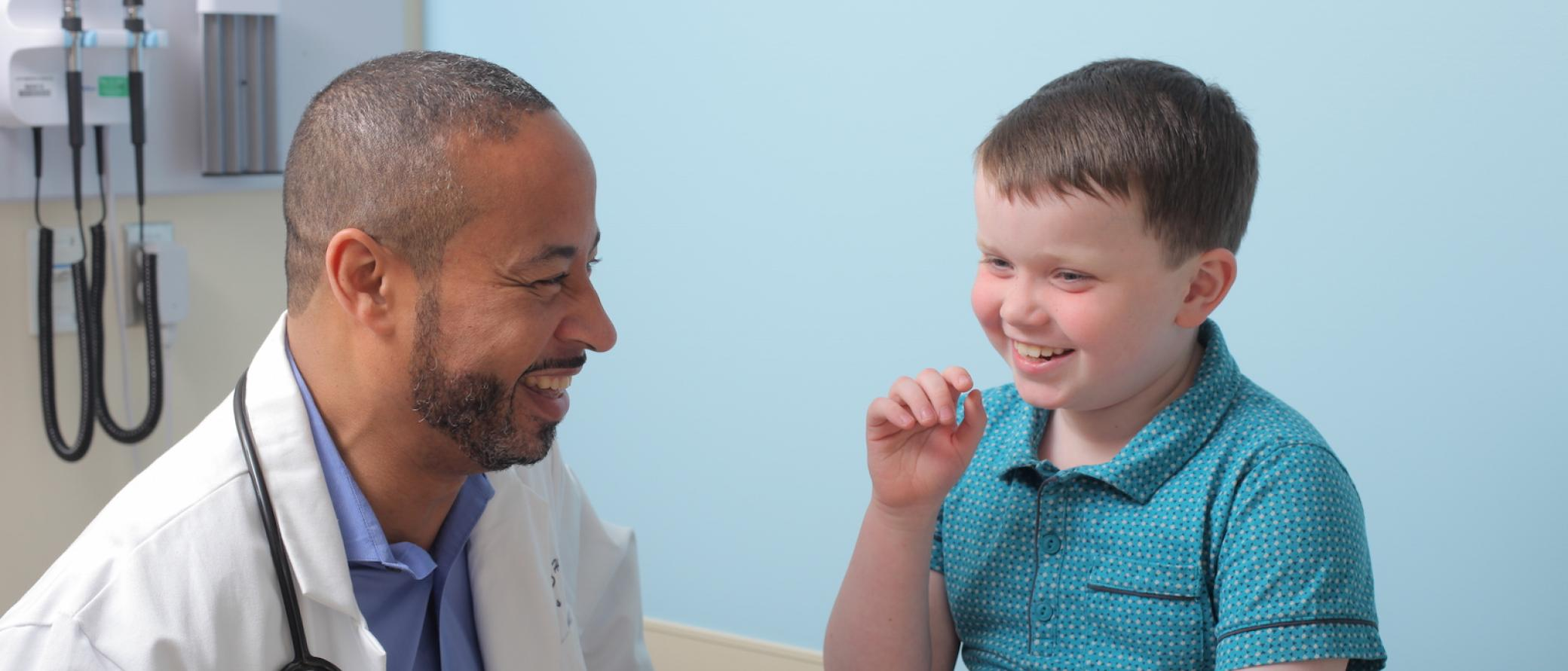 A doctor laughs with a little boy in a doctor's office.