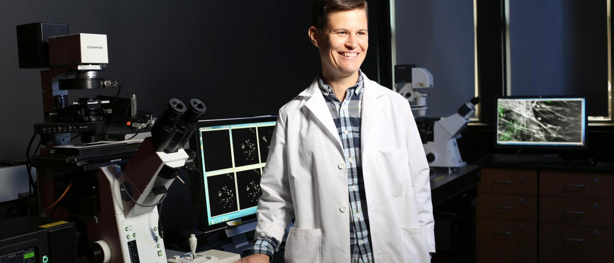 Female research scientist stands next to microscope.