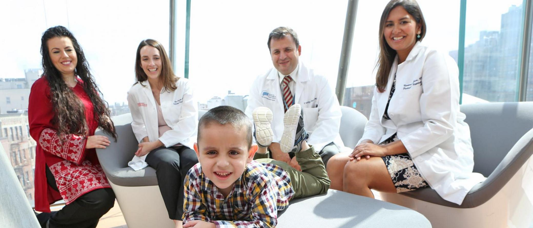 Young boy surrounded by his doctors and nurse.